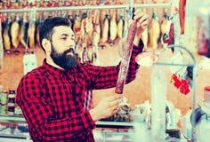 Сосиски молодого мужского клиента рассматривая в butcher's ходят по магазинам Стоковая Фотография RF