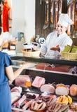 Сосиски продавца предлагая к молодой женщине в магазине деликатеса Стоковые Изображения RF