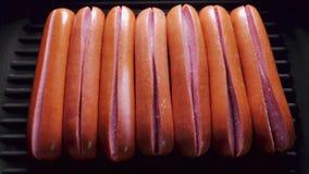 Сосиски раскрывают на сковороде из-за температуры, зажаренных в духовке кудрявых сосисках, timelapse еды варя, фаст-фуде видеоматериал