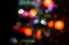 Сосна рождества defocused Красочные света гирлянды сверкнают на предпосылке Красные, голубые, и желтые электрические света Стоковые Фото