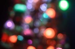 Сосна рождества defocused Красочные света гирлянды сверкнают на предпосылке Красные, голубые, и желтые электрические света Стоковое Фото