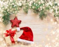Сосна, шляпа santa и коробка подарка на деревянной предпосылке Стоковые Изображения RF