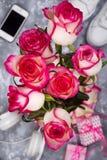Составленный роз и мобильного телефона на задней части расплывчатой предпосылки Стоковое Фото