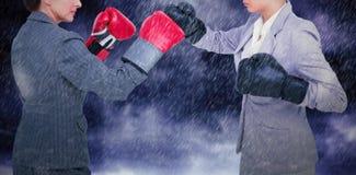 Составное изображение агрессивных коммерсанток кладя в коробку над белой предпосылкой Стоковые Изображения