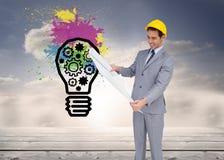 Составное изображение архитектора при трудная шляпа смотря планы Стоковое Изображение