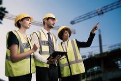 Составное изображение архитекторов в отражательной одежде смотря отсутствующий пока планшет Стоковое Фото