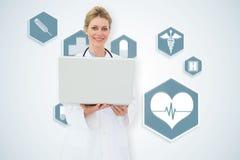 Составное изображение белокурого доктора используя компьтер-книжку Стоковое фото RF