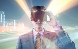 Составное изображение бизнесмена в костюме используя шлемофон виртуальной реальности Стоковое фото RF