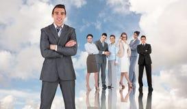 Составное изображение бизнесмена в сером костюме усмехаясь на камере Стоковое фото RF