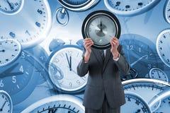 Составное изображение бизнесмена держа часы перед его стороной Стоковое Фото