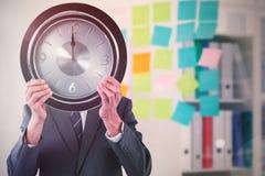 Составное изображение бизнесмена держа часы перед его стороной Стоковое Изображение