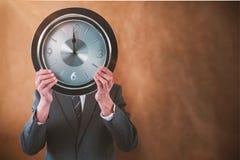 Составное изображение бизнесмена держа часы перед его стороной Стоковая Фотография