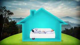 Составное изображение бизнесмена лежа на софе используя его компьтер-книжку усмехаясь на камере Стоковая Фотография RF