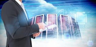 Составное изображение бизнесмена используя его ПК таблетки Стоковая Фотография
