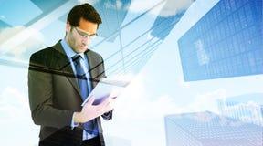 Составное изображение бизнесмена используя планшет Стоковое фото RF