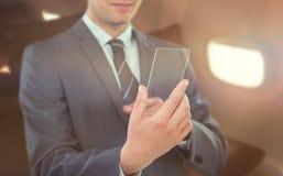 Составное изображение бизнесмена используя футуристический мобильный телефон Стоковая Фотография RF