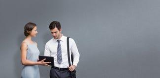 Составное изображение бизнесмена касается на экране пока женщина держит таблетку Стоковое Фото