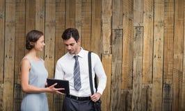 Составное изображение бизнесмена касается на экране пока женщина держит таблетку Стоковые Изображения RF