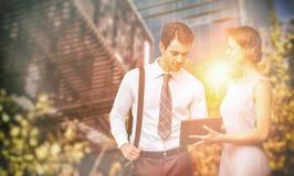Составное изображение бизнесмена касается на экране пока женщина держит таблетку Стоковые Фотографии RF