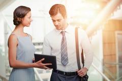 Составное изображение бизнесмена касается на экране пока женщина держит таблетку Стоковые Фото