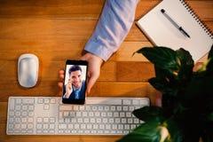 Составное изображение бизнесмена сидя звоня усмехаясь на камере Стоковое Фото