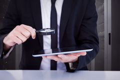 Составное изображение бизнесмена смотря его таблетку через лупу Стоковое Изображение