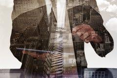 Составное изображение бизнесмена смотря его таблетку через лупу Стоковое фото RF