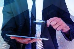 Составное изображение бизнесмена смотря его таблетку через лупу Стоковое Изображение RF