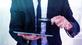 Составное изображение бизнесмена смотря его таблетку через лупу Стоковые Изображения