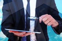 Составное изображение бизнесмена смотря его таблетку через лупу Стоковые Фотографии RF