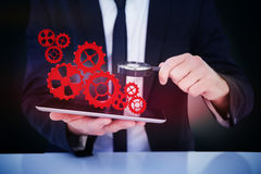 Составное изображение бизнесмена смотря его таблетку через лупу Стоковые Фото