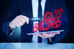 Составное изображение бизнесмена смотря его таблетку через лупу Стоковая Фотография RF