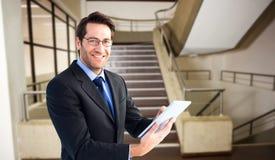 Составное изображение бизнесмена смотря камеру пока использующ его таблетку Стоковые Изображения