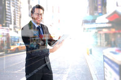 Составное изображение бизнесмена смотря камеру пока использующ его таблетку Стоковое Изображение RF