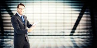 Составное изображение бизнесмена смотря камеру пока использующ его таблетку Стоковые Изображения RF