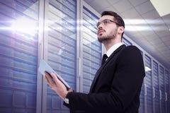 Составное изображение бизнесмена смотря отсутствующее пока использующ таблетку Стоковое Изображение