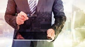 Составное изображение бизнесмена смотря таблетку с лупой Стоковое фото RF