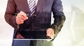 Составное изображение бизнесмена смотря таблетку с лупой Стоковые Изображения