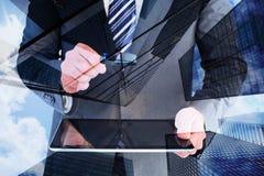 Составное изображение бизнесмена смотря таблетку с лупой Стоковая Фотография