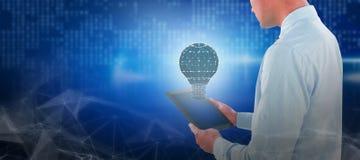Составное изображение бизнесмена смотря цифровую таблетку Стоковое фото RF