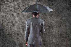 Составное изображение бизнесмена стоя под зонтиком Стоковое Изображение