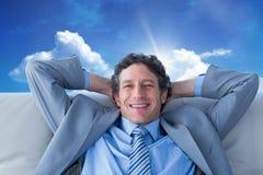 Составное изображение бизнесмена усмехаясь на камере сидя на кресле Стоковая Фотография RF