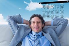 Составное изображение бизнесмена усмехаясь на камере сидя на кресле Стоковая Фотография