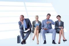 Составное изображение бизнесменов ждать быть вызванным в интервью Стоковая Фотография