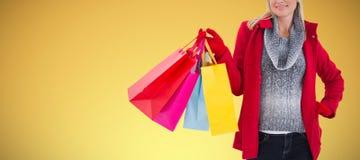 Составное изображение блондинкы в зиме одевает держать хозяйственные сумки стоковые изображения rf