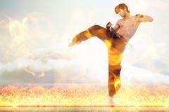 Составное изображение бойца боевых искусств над огнем пылает Стоковые Изображения RF