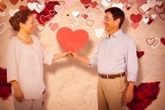 Составное изображение более старых азиатских пар держа сердце Стоковое Изображение RF