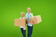 Составное изображение более старых пар усмехаясь на камере держа moving коробки Стоковые Изображения RF