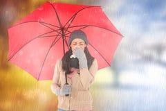 Составное изображение больного брюнет дуя ее нос пока держащ зонтик Стоковое Изображение RF