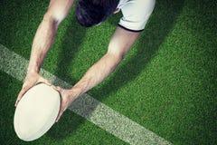 Составное изображение взгляда высокого угла человека держа шарик рэгби с обеими руками Стоковое Фото